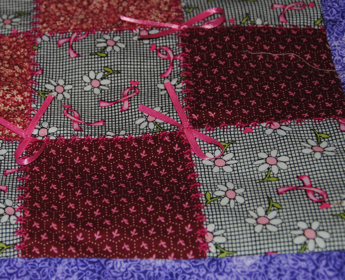A close-up of the breast cancer square.  The only new fabric is the breast cancer daisy and hearts, the others were from her stash.
