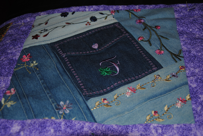 "This square was made with the decorated denim blouses,including the pocket.  I added the ""F"" for Field in purple, her favorite color, along with a green shamrock.  Due to her height and red hair, my husband always called my mother'n law ""Lep"" short for leprecan."