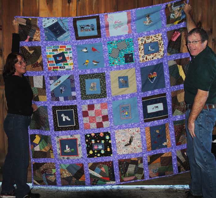 My husband and I holding up the quilt at the family reunion 2013